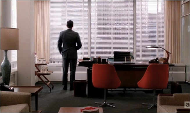 Don standing in his slick modernist office staring out at a sea of skyscrapers